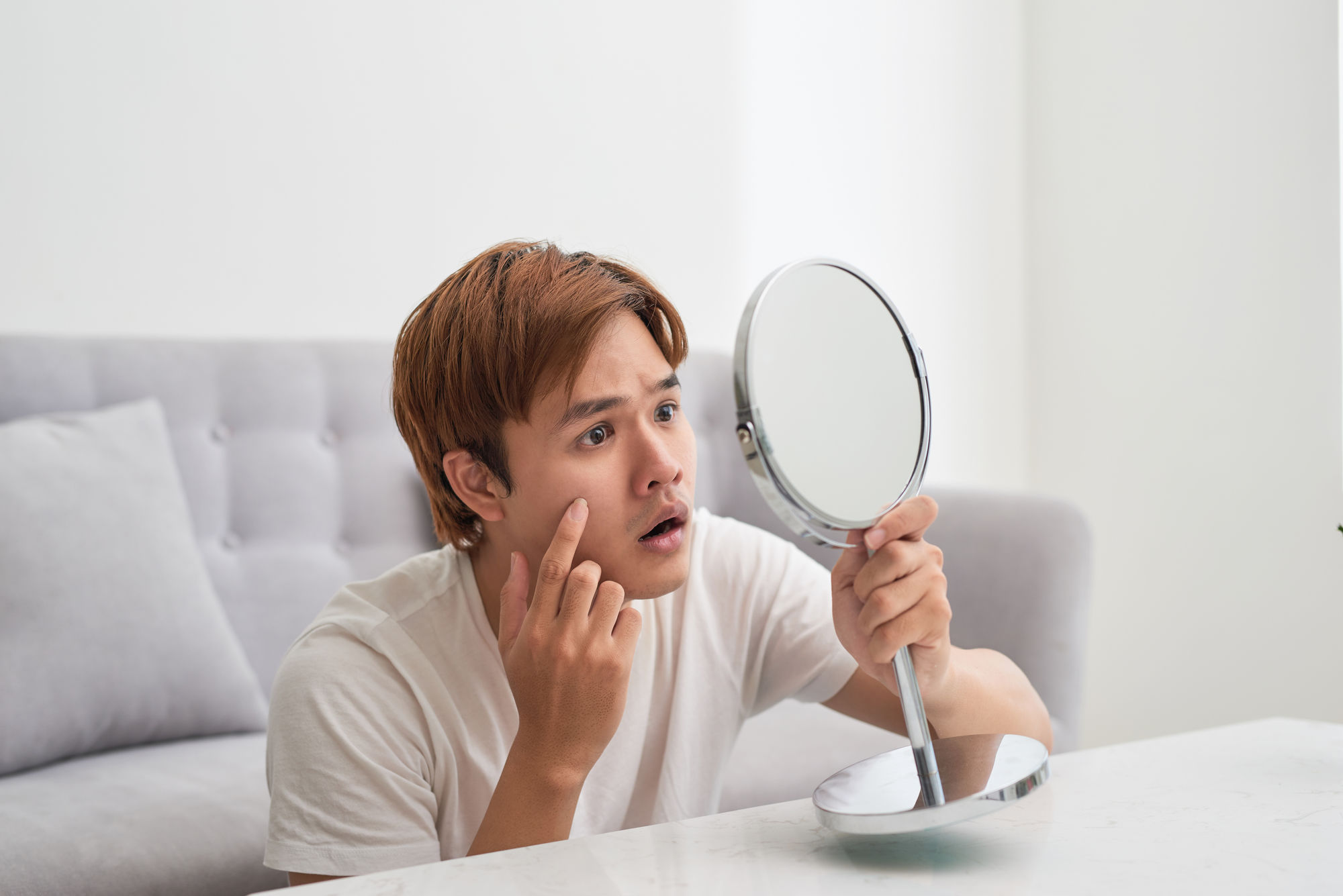 Handsome man looking at himself in mirror. Squeezing pimple.