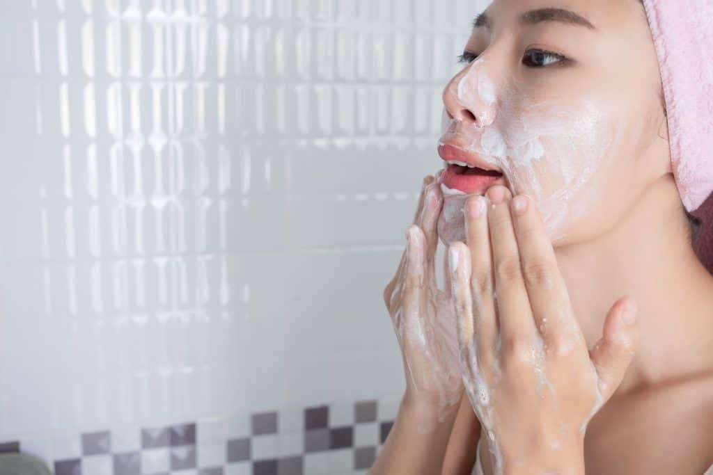 a woman cleaning her face thoroughly with facewash