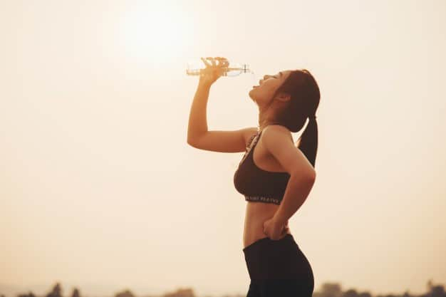a woman drinking water her run